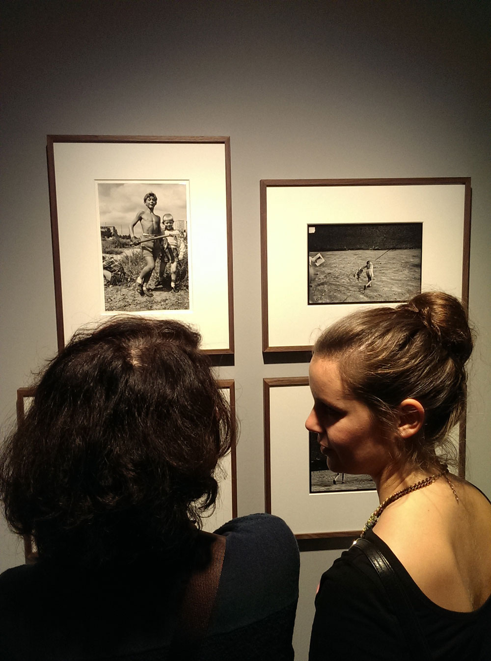 """Vernissage visitors looking at """"Jungen beim Spielen in Charlottenburg"""" (Boys playing in Charlottenburg) from 1957 (top left) at the Will McBride exhibition."""