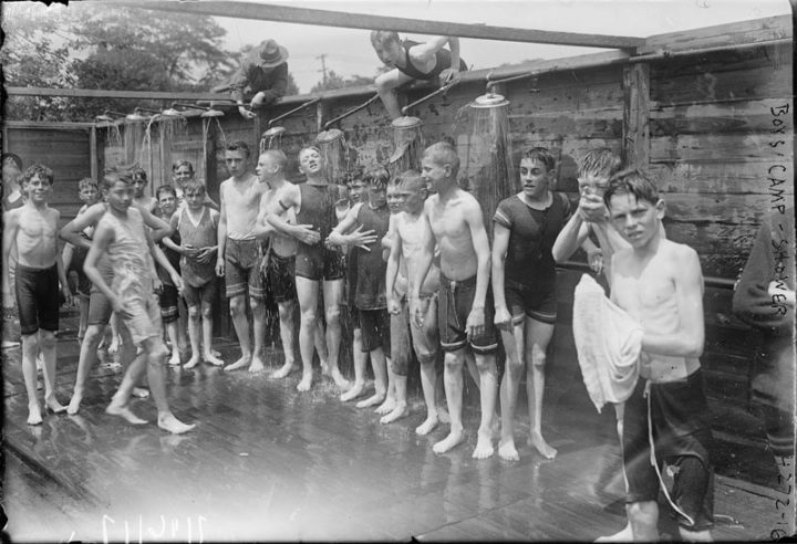 Scene from a public bath with shirtless boys, vintage photograph